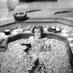 Myrna Loy in a bath of flowers, equally as urgent as the devastation of tenant families during the Great Depression. (Photo from the set of the 1933 film, The Barbarian.)