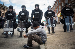 Baltimore, 2015: Daquan Green, age 17, sits on the curb while riot police stand guard after the funeral of Freddie Gray.(Photo by Andrew Burton/Getty Images)
