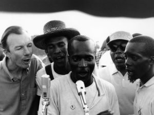 "American folk singer and activist Pete Seeger (left) adopted and helped popularize ""We Shall Overcome"" by teaching the song at rallies and protests. Here he sings with activists in Greenwood, Miss., in 1963. Adger Cowans/Getty Images"